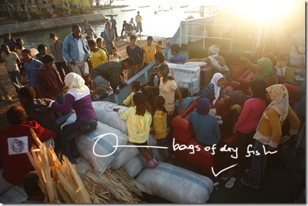 anxious passengers on bags of dry fish